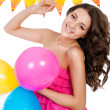 Stock Photo: Young girl with bright balloons and cake