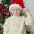 Little boy in santa hat near Christmas tree — Stock Photo #36748591
