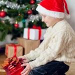 Little boy in santa hat near Christmas tree — Stock Photo #36748687