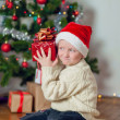 Little boy in santa hat near Christmas tree — Stock Photo