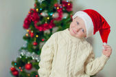 Little boy in santa hat near Christmas tree — Stockfoto