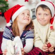 Little boy and girl in santa hat near Christmas tree with gifts — Stock Photo