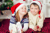 Little boy and girl in santa hat near Christmas tree with gifts — Stockfoto