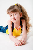 Little girl in jeans on a white background — Stock Photo