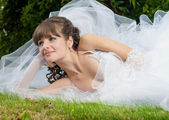 Beautiful bride in wedding dress on nature — Stock Photo
