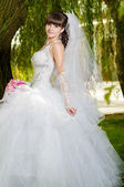 Beautiful bride in wedding dress with a bouquet of flowers on nature — Stock Photo