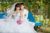 Young and beautiful bride and groom on the bench — Stock Photo