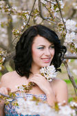 Beautiful girl in spring blooming garden — Stock Photo