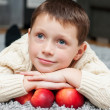 Stock Photo: Boy with apples lies on carpet at home