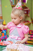 Little girl eating cake on birthday party — Stock Photo