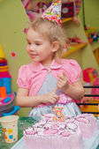 Little girl with birthday cake on birthday party — Stok fotoğraf