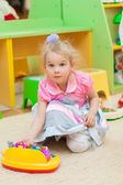 Little girl with toys in the playroom — Foto de Stock