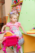 Little girl with toys in the playroom — Stock Photo