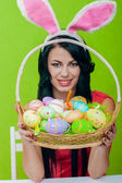 Beautiful girl with a basket of Easter eggs — Stockfoto