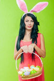 Beautiful girl with a basket of Easter eggs — Stok fotoğraf