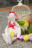Easter toy bunny with colored eggs — Stock Photo