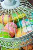 Decorative cage with painted Easter eggs — Stock Photo