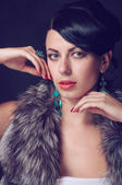 Young woman in a fur coat in  earrings — Stock Photo