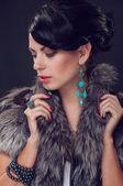 Young woman in a fur coat in  earrings — 图库照片