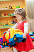 Little girl playing with toys in  playroom — Photo