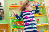 Little girl playing with toys in  playroom — Stock Photo