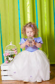 Little girl in a beautiful dress with  birdcages — Stock Photo