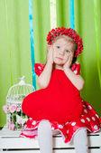 Vacker liten flicka i en röd klänning med ett rött hjärta kudde — Stockfoto