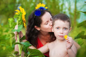 Mother and son in a field of sunflowers in summer — Foto Stock