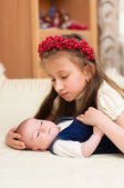 Older sister hugging baby lying — Foto Stock