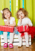 Little girls in fluffy skirts with gift boxes — Stock Photo