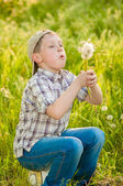 Boy on summer nature with dandelions — Stock Photo