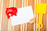 Paper card and seashells toy shovel on wood — Stockfoto