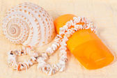 Bottle of shampoo and towel seashells, shell beads — Stock Photo