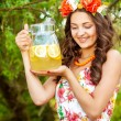 Young beautiful girl in a wreath of flowers with lemonade — Stock Photo #48459869