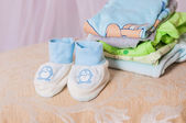 Baby booties and clothes folded — Stock Photo