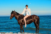 Young beautiful girl with a horse on the beach — Stockfoto