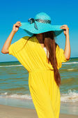 Beautiful girl with long hair on the beach in a blue hat — Stock Photo