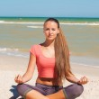 Beautiful girl is engaged in yoga on the beach — Stock Photo #51015243