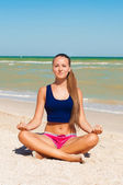Beautiful girl is engaged in yoga on the beach — Stock Photo