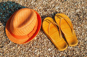 Bright summer hat and sandals on the beach — Stock Photo