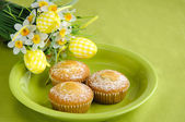 Easter cakes on plate with flowers on green — Stok fotoğraf