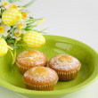 Easter cakes on plate with flowers on white — Stock Photo
