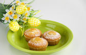 Easter cakes on plate with flowers on white — Stok fotoğraf