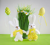 Easter funny bunnies with eggs and flowers — Stock Photo