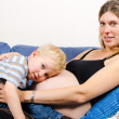 Smiling pregnant mother with her little boy on sofa — Stock Photo