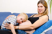 Smiling pregnant mother with her little boy on sofa — Stok fotoğraf