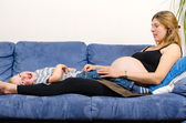 Smiling pregnant mother with her little boy on sofa — Stock fotografie