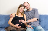 Happy husband embracing his pregnant wife on couch — Stockfoto