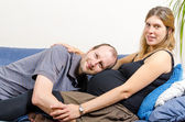 Happy husband embracing his pregnant wife on couch — Stok fotoğraf