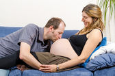 Happy husband kissing tummy of his pregnant wife on couch — Stock fotografie